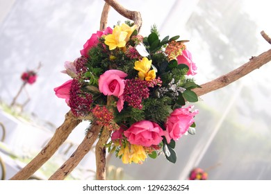Summery floral centrepiece with pink roses and yellow freesias attached to a rustic wooden tripod frame.