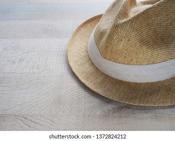 Summery straw hat left on the wooden table