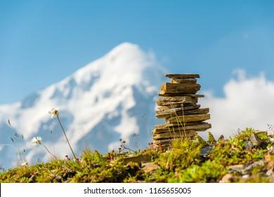 Summit cairn - stacked rocks ahead of snow mountain peaks