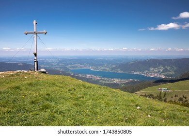 Summit cross on the Hirschberg peak in Bavaria, Germany, with lake Tegernsee