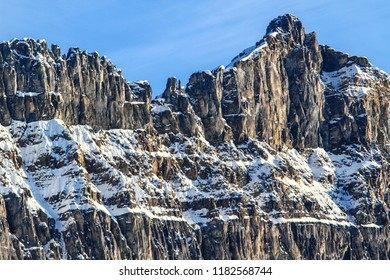 The summit ridge of a rocky mountain with a light covering of snow showing off the texture of the cliff face.