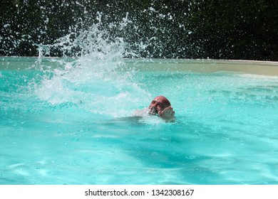SummMan swimming in a pool splashing the water in the air.er series.
