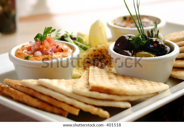 Sumptious platter of flat breads served with red pepper hummus dip, crab dip, olives and grilled haloumi cheese. Shallow DOF.