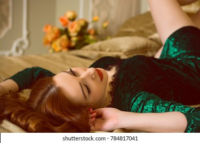A sumptuous woman in Victorian style interior in bed at the bedroom, dressed in velvet green long emerald foamy gown. The concept of femininity and attractiveness