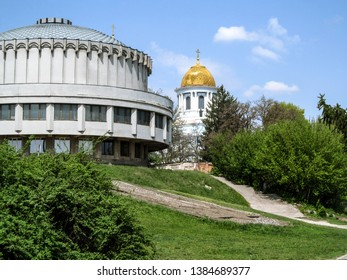 Sumy, Ukraine - April 28, 2019: Golden Dome of Savior-Transfiguration Cathedral and the rotunda of Palace of Children and Youth in Sumy, back view. Beautiful spring landscape with two round buildings