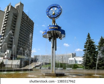 Sumy, Ukraine - April 28, 2019: Large fountain 'European' near multi-storey building in Sumy on a sunny day. Metal construction from pipes with symbolized European Union flag and coat of arms of Sumy