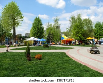 """Sumy, Ukraine - April 28, 2019: People relax in children's park """"Fairy Tale"""" in Sumy in spring holiday. Beautiful background with copy space, people walk among stalls and amusements in a public park"""