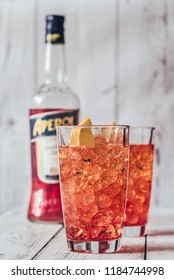 SUMY, UKRAINE - AUGUST 29, 2018: Glass of Aperol Spritz cocktail with bottle of Aperol on the white wooden background. Aperol is famous Italian aperitif.