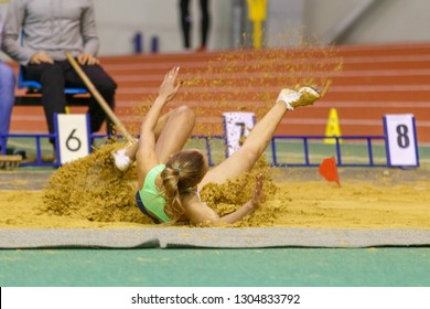 SUMY, UKRAINE - JANUARY 25, 2019: female athlete landing in sandpit in her attempt in long jump competition on Team Ukrainian indoor track and field championship 2019.