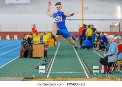 SUMY, UKRAINE - JANUARY 25, 2019: male athlete performing his attempt in long jump competition on Team Ukrainian indoor track and field championship 2019.