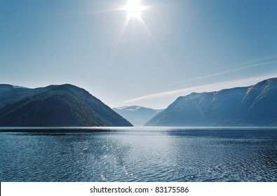 Sun above mountains, fjord in the Norway.