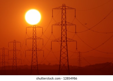 Sun above a row of electricity pylons