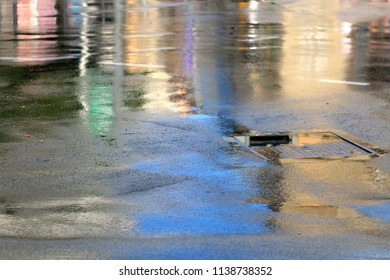 Sun after the storm - colorful lights reflecting in the rain soaked street.