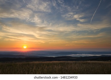 Sun after sunrise with slightly cloudy sky above hills, forests and meadows