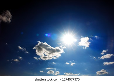 Sun against blue sky with white clouds