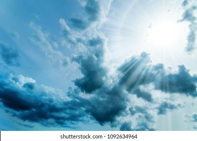The sun appears between dark clouds; Clouded sky with sunrays; Dark cloudiness and bright sunlight; Autumn sky