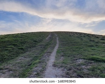 The sun attempts to be seen over the crest of a steep hill in the South Downs of Sussex, England. Large, interesting clouds dance and stream across the blue sky, attempting to draw focus from the fre