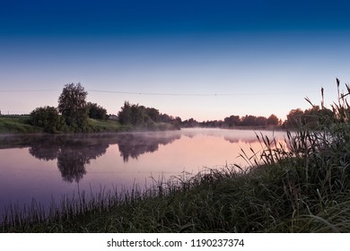 The sun barely sets behind the horizon on a summer night by a river in the rural Finland. The nights are very light this time of the year.