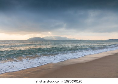 Sun beam shining through the stormy sky over Nha Trang beach, Vietnam.