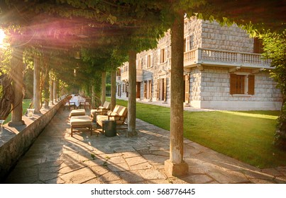 Sun beams and beautiful italian mansion with outdoor cafe on summer terrace (Italy)