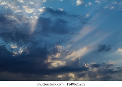 Sun beams with blue and white clouds on a summer morning