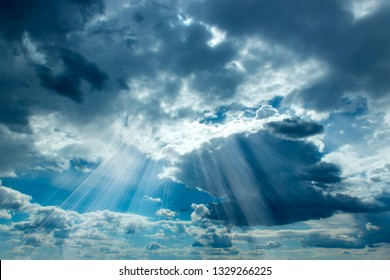 Sun beams breaking through the dark clouds at sunset. Hope, prayer, God's mercy. Beautiful spectacular conceptual meditation background.