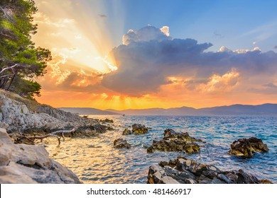 Sun beams or light rays breaking through the dark clouds at sunset, over the sea. Hope, prayer, peace, God's grace. Beautiful spectacular conceptual meditation background.