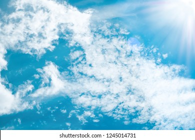 Sun beams lighting white clouds in bright blue sky. For background and wallpaper