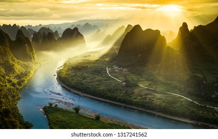 Sun beams on a misty morning on karst mountains and river Li in Guilin/Guangxi region of China