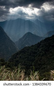 Sun beams out of dark clouds above silhouetted mountains, taiwan