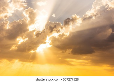 Sun beams or rays breaking through the dark clouds at sunset. Hope, prayer, God's mercy and grace. Beautiful spectacular conceptual meditation background. Artistic golden sunset edit.