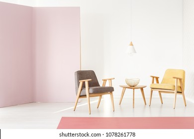 Sun beams shining on a modern, wooden armchair in a classy pastel pink interior with white wall - furniture arrangement for a brochure