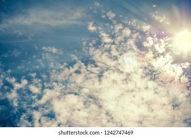 Sun beams shining through white clouds in bright blue sky. Vintage colors. For background and wallpaper