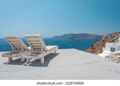 Sun beds on the roof with an amazing view over of the beautiful Mediterranean Sea. Viewing platform at Santorini, Greece. Holidays, honeymoon and vacation concept. Travel in Europe.