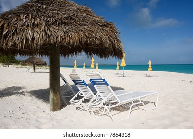sun beds with thatched sun shade on beach with turquoise sea