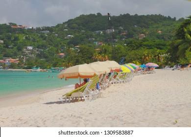 Sun beds and umbrellas on sand beach. St. George's, Grenada