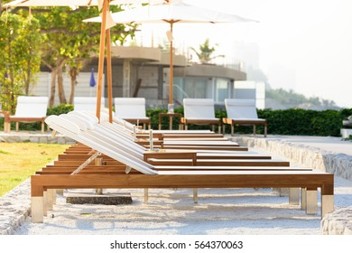 Sun beds and umbrellas at the poolside.