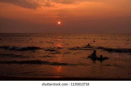The sun before setting. Just above the horizon. above the sea. Kids bathing and  playing in the water. Beautiful yellow evening sky.