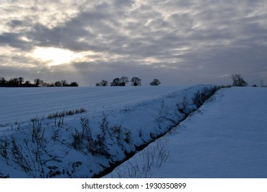 Sun behind clouds over fields covered in heavy snow in the English countryside