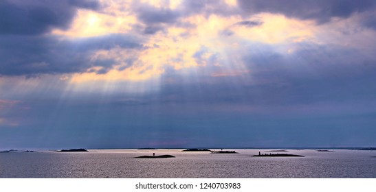 The sun behind the clouds with rays of light shining down on sea. Sky background. Photo in artistic style.