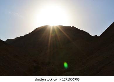 Sun behind mountain, Qumran caves in Qumran National Park, Judean desert hike, Israel