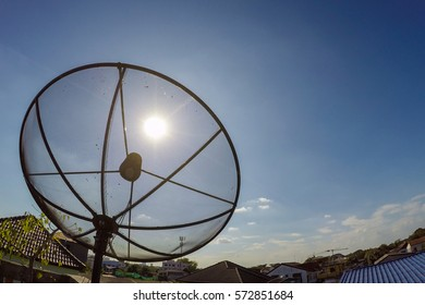 Sun behind parabolic satellite receiver dish with beam with blue sky