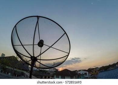 Sun behind parabolic satellite receiver dish in twilight time