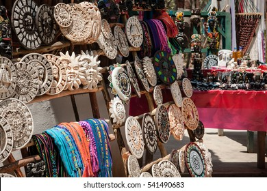 A sun between handicraft objects of Mayan and religious culture for sale