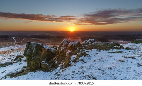 The sun breaking the horizon behind the rocks of a snowy Bradgate Park.