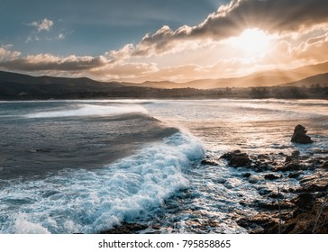 Sun breaking through the clouds onto a turbulent Mediterranean sea at Lozari beach in the Balagne region of Corisca following a winter storm