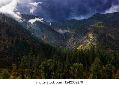 Sun breaking through stormy sky over rugged rocky mountains, Autumn