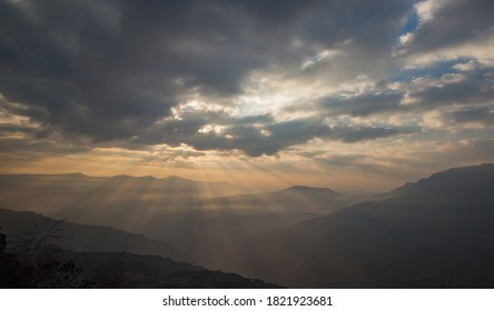 Sun breaking through veil of clouds in himalayan hills. hills silhouetted.