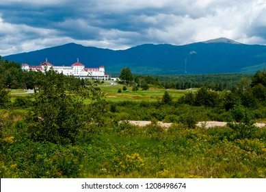 Sun breaks through clouds over Mount Washington and hotel in New Hampshire White Mountains.