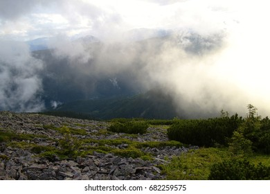 The sun breaks through the fog and clouds in the mountains